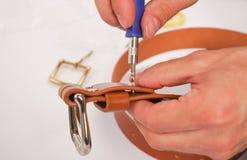 L'uomo fa dalla cinghia di cuoio delle mani con il fermaglio Hobby fatto a mano giovane che riposa dalla fabbricazione le sue cin fotografia stock