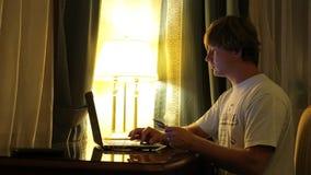 L'uomo fa gli acquisti sopra Internet su un computer e paga dalla carta di credito a casa stock footage