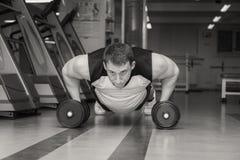 L'uomo fa gli esercizi con le teste di legno Fotografie Stock