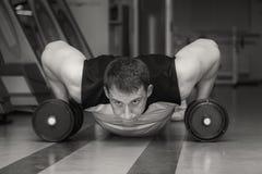 L'uomo fa gli esercizi con le teste di legno Fotografia Stock