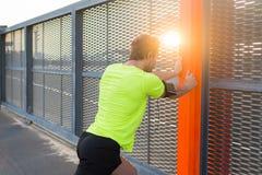 L'uomo fa gli esercizi per le gambe prima ha cominciato il suo funzionamento all'alba Immagini Stock Libere da Diritti