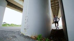 L'uomo fa il trucco sotto il ponte, movimento lento stock footage