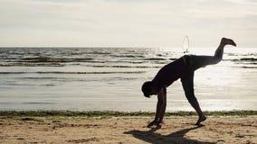 L'uomo fa la vibrazione acrobatica sulla spiaggia in macchina fotografica anteriore Onde vacanza Albero nel campo video d archivio