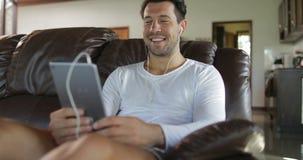 L'uomo fa la video chiamata online facendo uso della stanza di Sit On Coach In Living del computer della compressa, Guy Speaking  archivi video