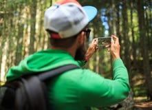 L'uomo fa le foto su uno smartphone nella foresta di conifere in fotografia stock