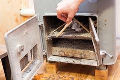 L'uomo fa un fuoco nella bio- caldaia solida del combustibile Fotografie Stock Libere da Diritti