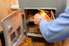 L'uomo fa un fuoco nella bio- caldaia solida del combustibile Fotografia Stock