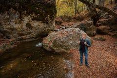L'uomo fa una pausa il fiume della montagna in autunno immagine stock libera da diritti