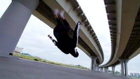 L'uomo fa una vibrazione indietro sotto il ponte, movimento lento stock footage