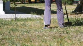 L'uomo falcia l'erba facendo uso di una falciatrice portatile al rallentatore stock footage