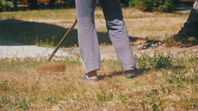 L'uomo falcia l'erba facendo uso di una falciatrice portatile al rallentatore archivi video