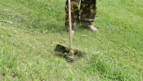 L'uomo falcia l'erba di sua estate del giardino stock footage