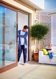 L'uomo felice apre i portelli scorrevoli del Th sul patio dell'estate Famiglia che si rilassa a casa immagine stock