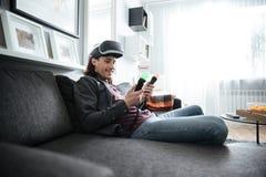 L'uomo felice che si siede a casa all'interno gioca Fotografie Stock