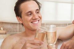 L'uomo felice con champagne tosta nella vasca Fotografia Stock
