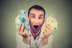 L'uomo felice con le euro banconote dei soldi estatiche celebra il successo Immagine Stock