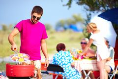 L'uomo felice cucina le verdure sulla griglia, picnic della famiglia Immagine Stock