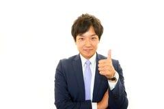 L'uomo felice di affari che mostra i pollici aumenta il segno Fotografia Stock