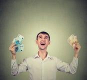 L'uomo felice estatico celebra le banconote delle fatture dell'euro dei soldi della tenuta di successo Immagini Stock