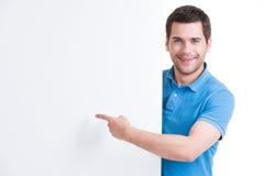 L'uomo felice indica il dito su un'insegna in bianco. Immagine Stock