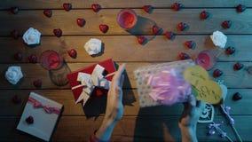 L'uomo felice prova a capire che cosa si trova dentro i suoi regali di festa e li scuote, vista superiore video d archivio