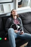 L'uomo felice si trova sul sofà a casa che tiene i vetri 3d Immagine Stock Libera da Diritti