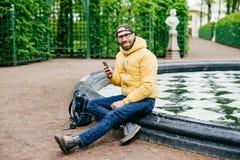 L'uomo felice sorridente con l'abbigliamento casual d'uso della setola e la grande seduta di occhiali hanno attraversato le gambe fotografia stock