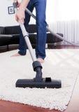 L'uomo felice sta pulendo nella stanza moderna con il vuoto. fotografie stock libere da diritti