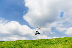 L'uomo felice sta saltando su un campo Fotografia Stock Libera da Diritti
