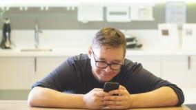 L'uomo felice utilizza il telefono nella sua cucina spaziosa per acquisto online stock footage