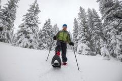 L'uomo felice va sulle racchette da neve giù la collina Fotografia Stock Libera da Diritti