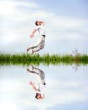 L'uomo felice in vestiti bianchi sta saltando Immagine Stock