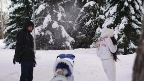 L'uomo felice, vestito in un rivestimento nero, un cappuccio sulla sua testa, pantaloni neri, getta la neve che vola alla sua mog stock footage