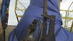 L'uomo fissa lo strumento sul tubo Rig Rotates Drilling Well archivi video