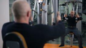 L'uomo forte nella palestra stringe le mani Riflessione nello specchio 4K Mo lento stock footage