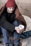 L'uomo freddo e senza tetto elemosina soldi Immagine Stock Libera da Diritti