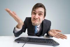 L'uomo frustrato ed incerto confuso sta lavorando con il computer fotografie stock libere da diritti