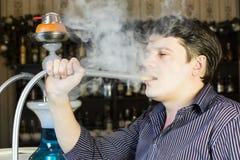 L'uomo fuma un narghilé Fotografie Stock