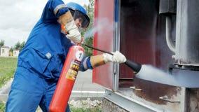 L'uomo funziona fino al modello del fuoco ed estingue la fiamma a concorrenza su erba archivi video