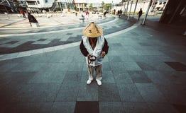 L'uomo giapponese che sta alla stazione anteriore per riceve la donazione dalla gente Fotografia Stock