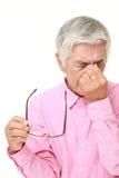 L'uomo giapponese senior soffre da astenopia Immagini Stock