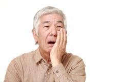 L'uomo giapponese senior soffre da mal di denti fotografia stock