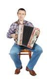 L'uomo gioca l'armonica che si siede su una sedia Fotografia Stock