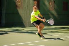 L'uomo gioca a tennis in panno luminoso Fotografia Stock