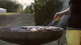 L'uomo gira le bistecche con le tenaglie sulla griglia archivi video