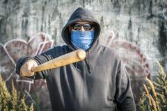 L'uomo giudica una mazza da baseball di andata su una parete Fotografia Stock
