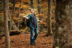 L'uomo gode delle foglie che cadono dagli alberi immagine stock