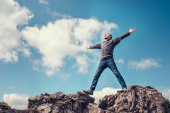 L'uomo gode di con il tatto di libertà sulla cima della montagna immagine stock