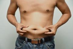 L'uomo grasso asiatico ha colesterolo Mostra il grasso in eccesso della pancia immagine stock