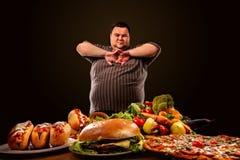 L'uomo grasso di dieta opera la scelta fra alimento sano e non sano Immagine Stock